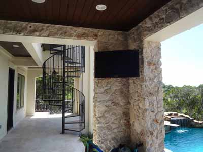 Custom TV Mounted with Speakers on the patio under the porch